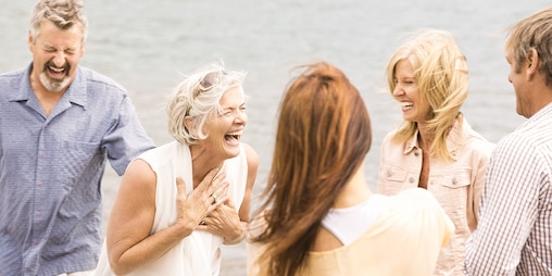 A group of people laughing on the beach