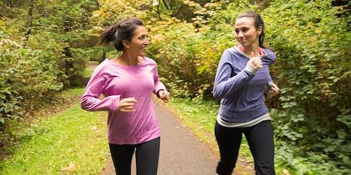 Een vrouwelijke jogger met oortjes in controleert de tijd op haar horloge