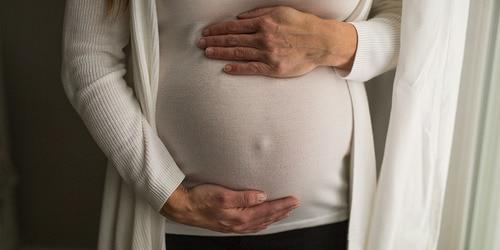 Trudnica se drži za stomak dok stoji pored prozora