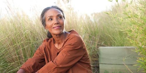 Eine ruhige ältere Dame sitzt auf einem sonnigen Feld, umgeben von hohem Gras
