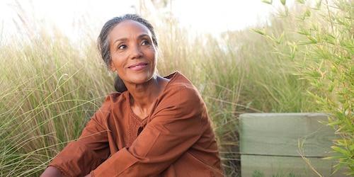 Una donna dall'aspetto sereno è seduta in un campo soleggiato, circondata dall'erba alta