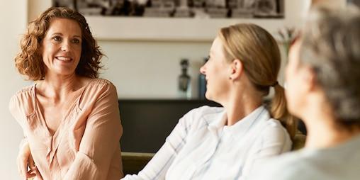 Drie volwassen vrouwen op een bank in een woonkamer die genieten van een goed gesprek