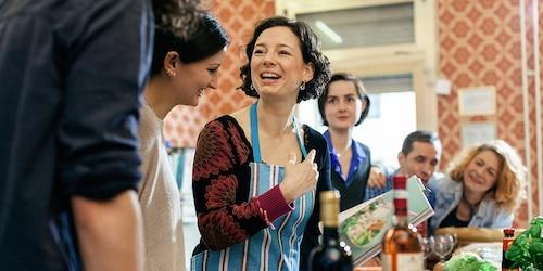Une professeure de cuisine entourée d'étudiants curieux dans une cuisine