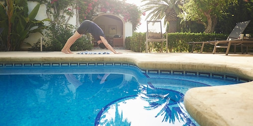 A woman doing yoga by the swimming pool