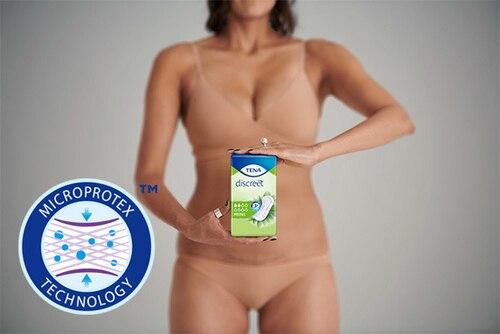 Donna in biacheria intima che mostra una confezione di TENA Discreet