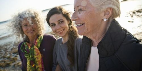 ثلاث سيدات على الشاطئ يبتسمن