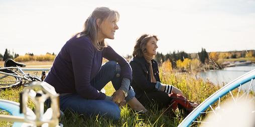 Δύο γυναίκες με ποδήλατα κάθονται στο γρασίδι και ξεκουράζονται στο ηλιόλουστο χωράφι.