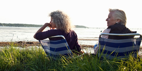 Two elderly women enjoy the view on a beach