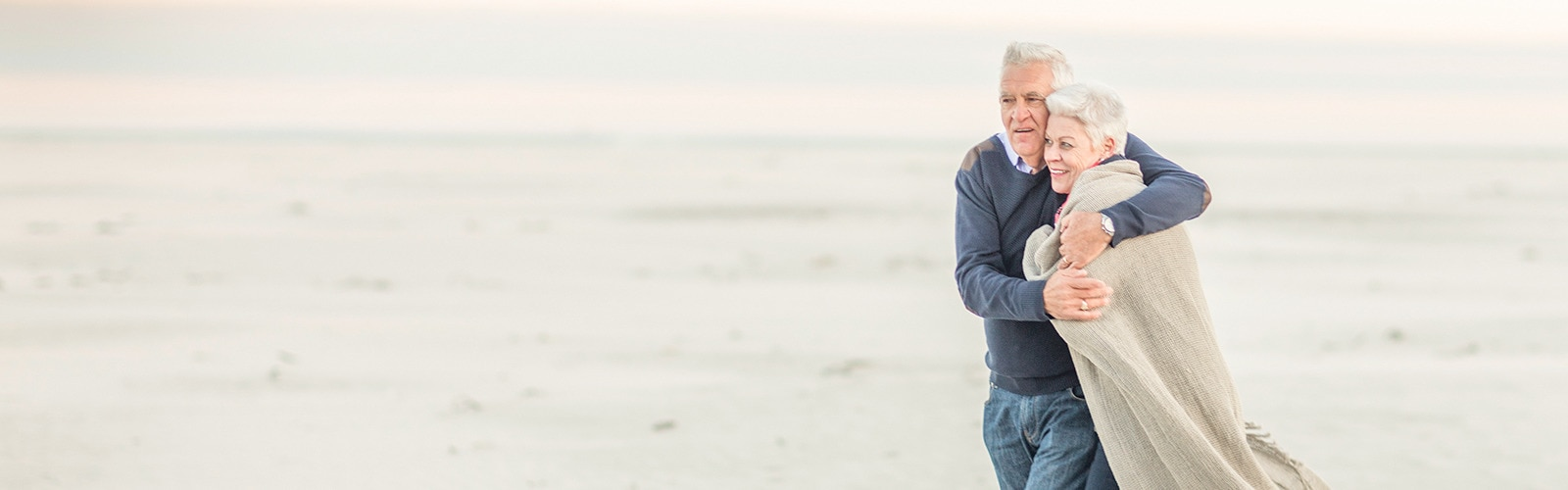 Elderly couple walking on the beach embracing