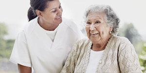 Caregiver and elderly woman laughing
