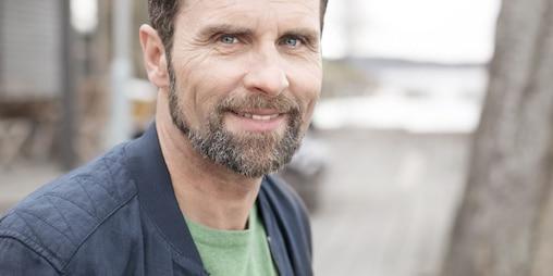 Bradat moški srednjih let se smeji v kamero