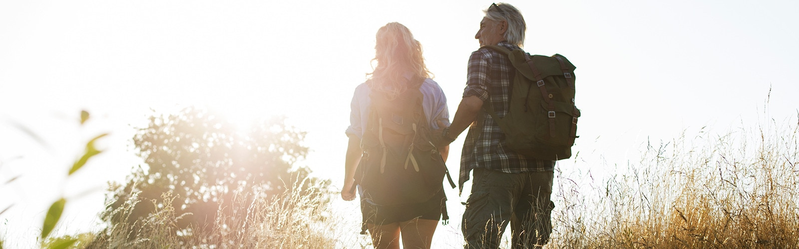 Mature man and woman hiking across a field
