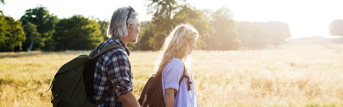 Žena i muškarac zrelih godina s ruksacima šeću kroz sunčano polje