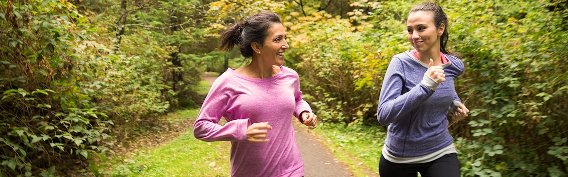 Dve ženski tečeta v gozdu
