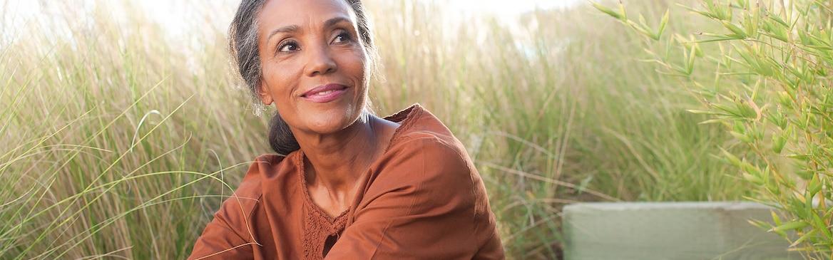 امرأة تجلس في حقل محاطة بالعشب العالي في يوم مشمس