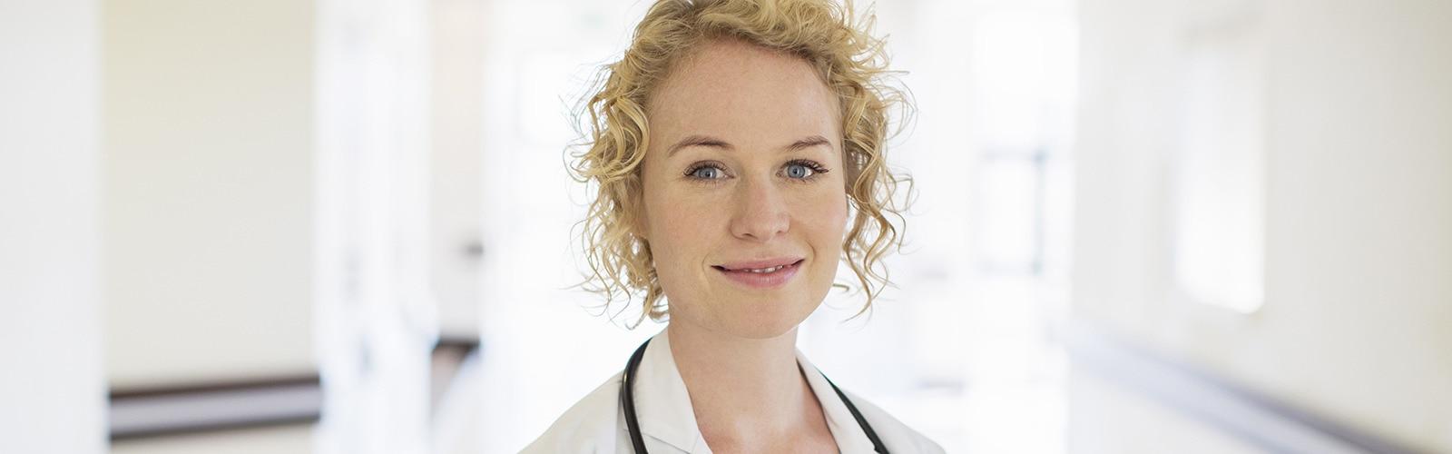 Eine blonde Ärztin mit Stethoskop steht auf einem Krankenhausflur und lächelt
