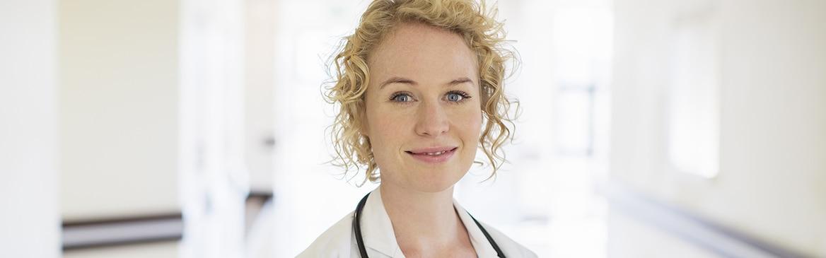 Uma médica loira com um estetoscópio sorri no corredor de um hospital