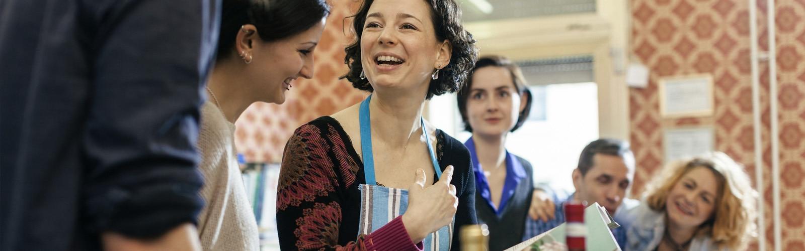 Μια γυναίκα δασκάλα μαγειρικής περιβάλλεται από περίεργους μαθητές σε μια κουζίνα