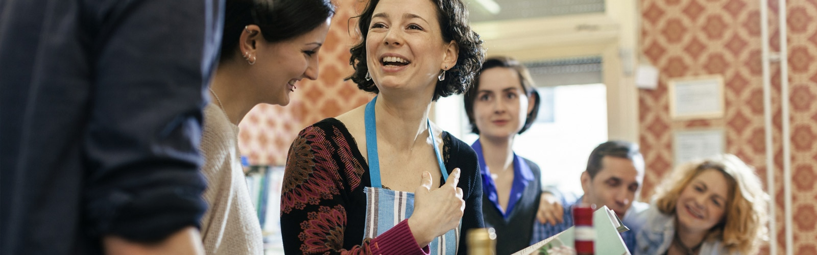 Učiteljica kuhanja je obkrožena z učenci v kuhinji