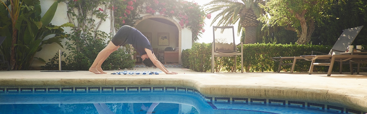 Woman doing yoga by a swimming pool