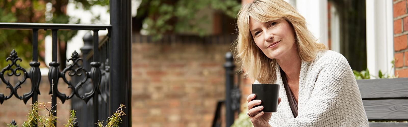 Žena si vychutnáva šálku čaju na terase pred tehlovým domom