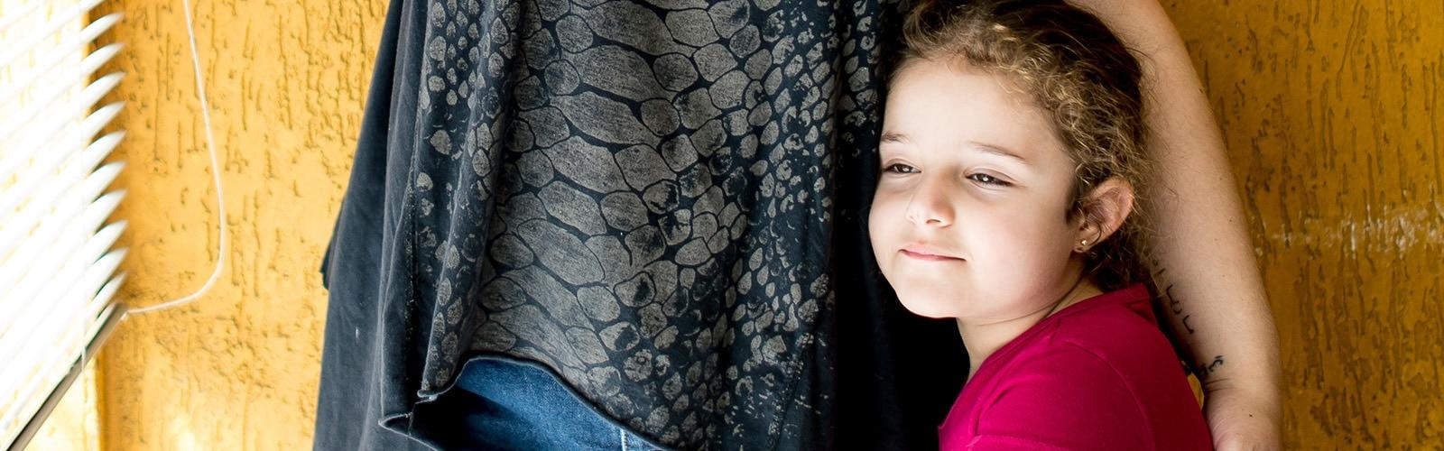 Äiti suojelee lämpimästi ja turvallisesti kainalossaan hymyilevää neljävuotiasta tyttöä huoneessa.