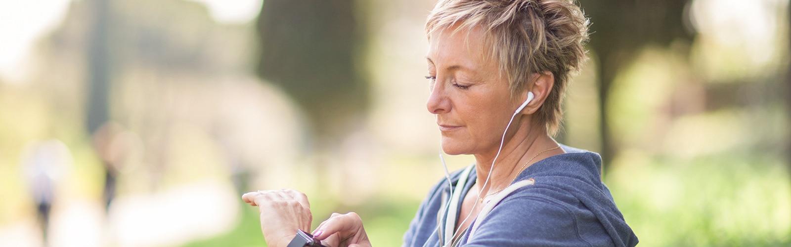Une joggeuse avec desécouteurs dans les oreilles regarde l'heure sur sa montre