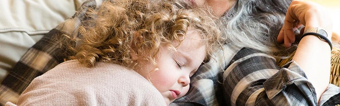 O fetiță de 3 ani cu păr blond și cârlionțat doarme în poala mamei sale