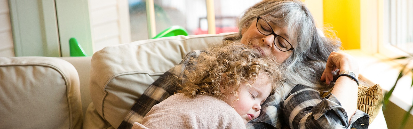 Little girl with curly hair sleeping on elderly woman with glasses