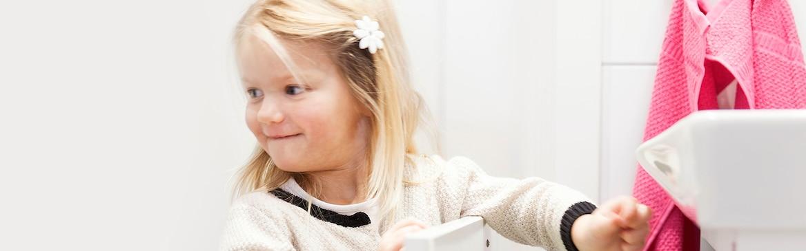 Odvažna trogodišnja djevojčica okreće se nekome dok otvara ladicu u kupaonici, ponosna što to može napraviti sama.