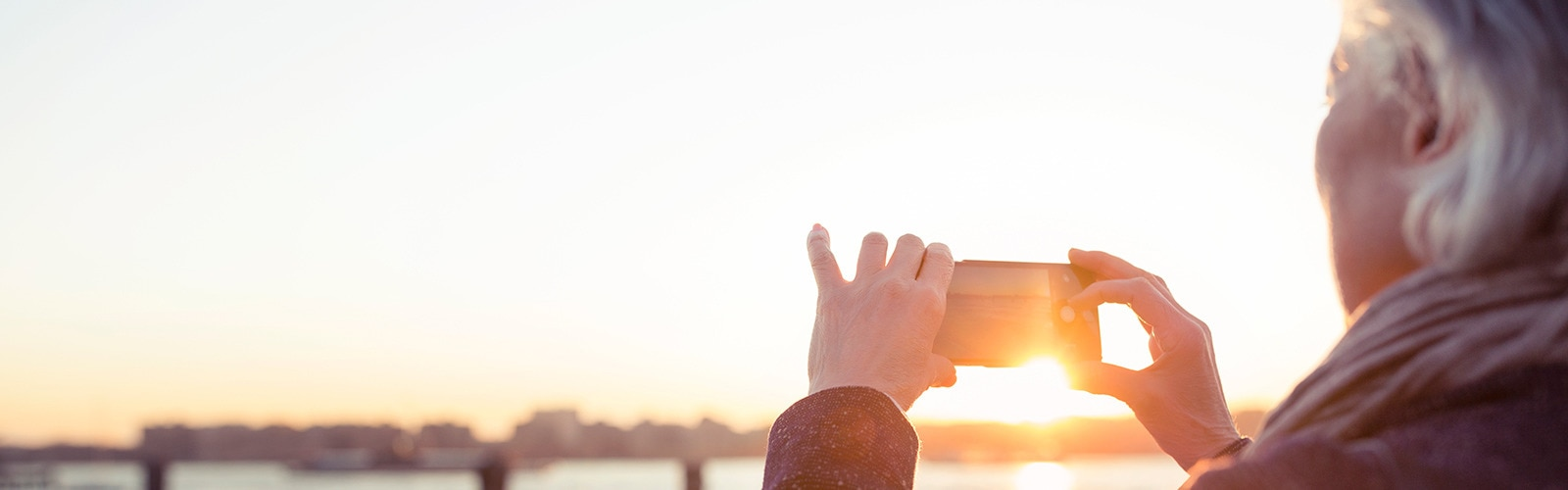 An elderly woman is photographing the sunset by the seaside