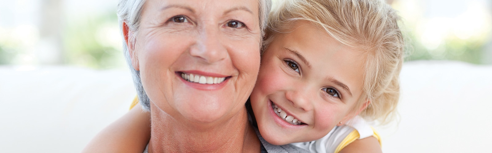 Uma mãe sorridente com o seu filho feliz e confiante a abraçá-la por trás.