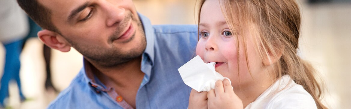 Uma menina de cinco anos senta-se ao colo do pai enquanto lhe limpa a cara com um lenço de papel.