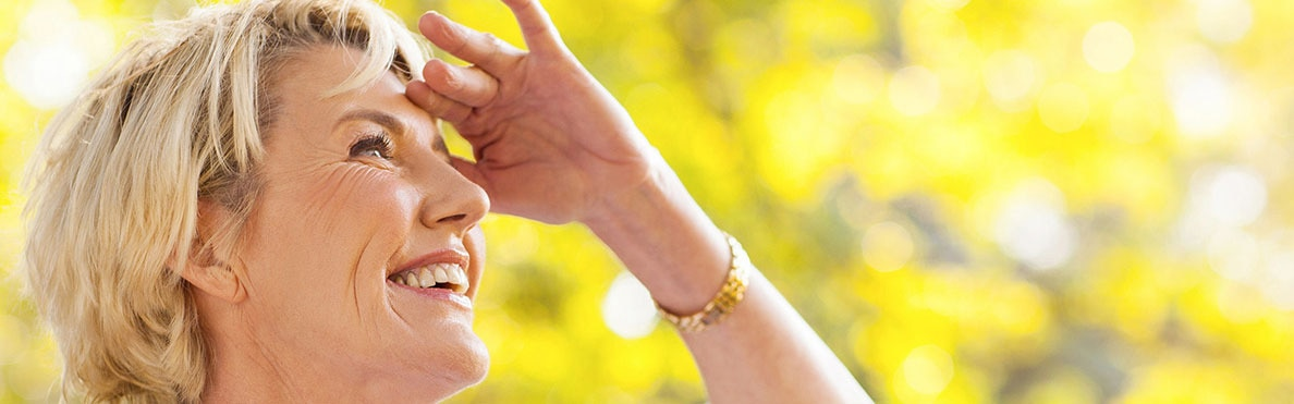 Una donna che sorride con mano sulla fronte