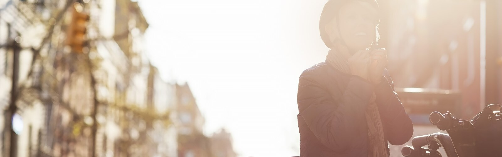 Šťastná zralá žena stojí ve města u kola a nasazuje si helmu