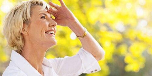 Donna bionda che sorride con mano sulla fronte per vedere meglio l'orizzonte
