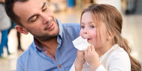 Young man with little girl wiping her face with a tissue