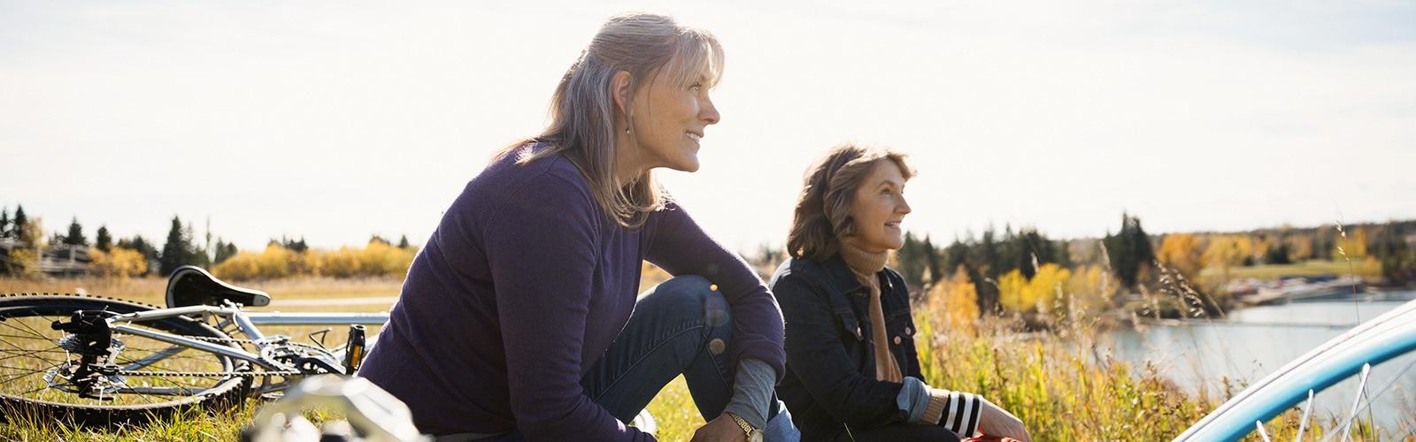 Zwei Frauen mit Fahrrädern sitzen im Gras und entspannen in der Sonne