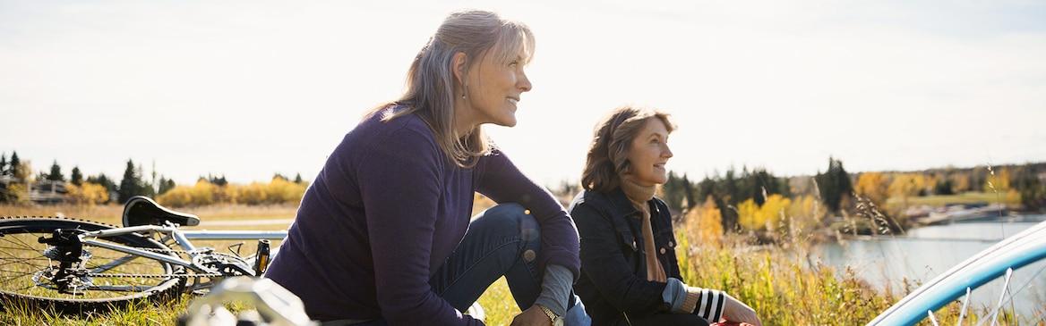 Deux femmes avec des vélos se reposent sur l'herbe dans un champ ensoleillé