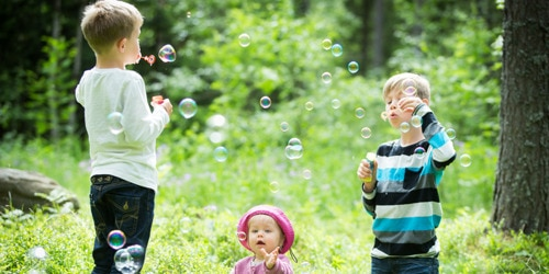Two young boys and a little girl blowing bubbles