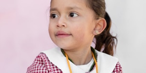 A little girl in her school uniform looks to the left