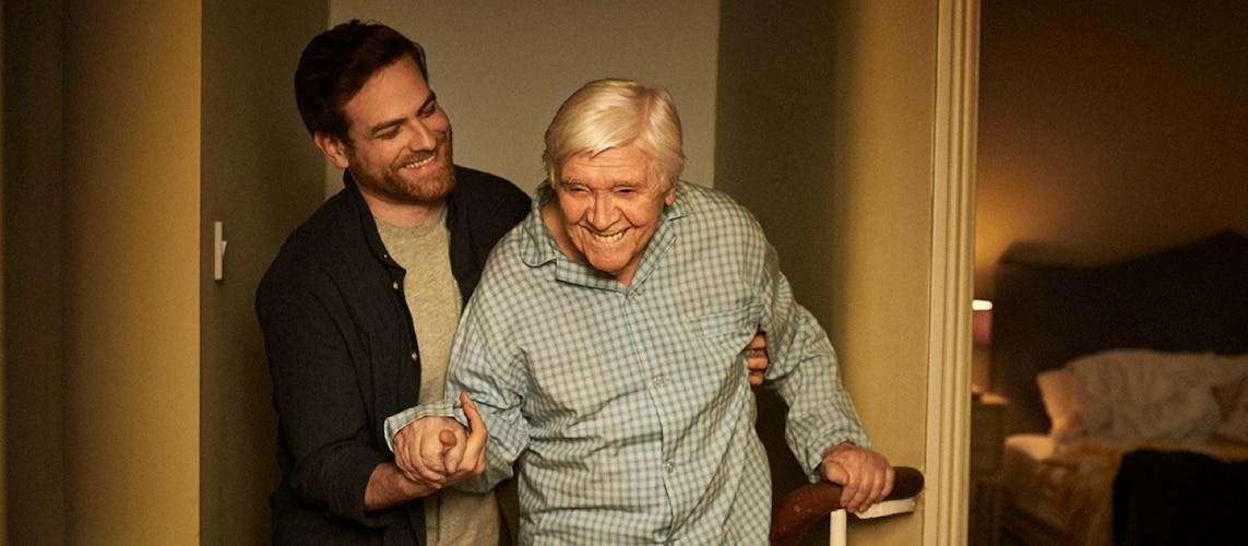Mężczyzna pomaga osobie starszej w przejściu w korytarzu.