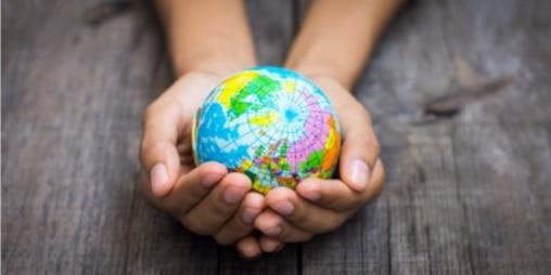 Дві руки тримають глобус, спираючись на дерев'яну поверхню
