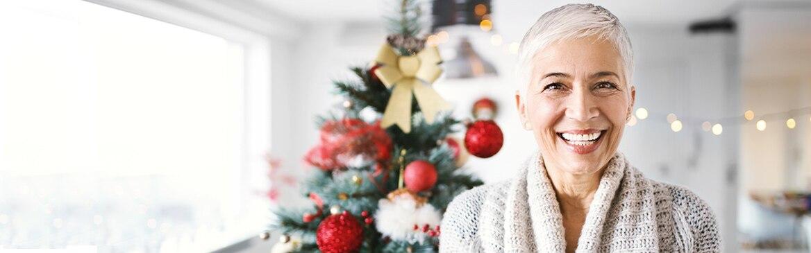 Una donna sorride con albero di Natale sullo sfondo