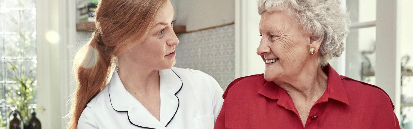 Nurse talking to a smiling elderly woman