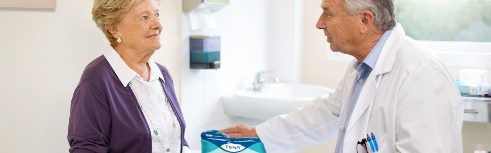 A doctor discusses TENA ProSkin Pants with his elderly female patient.