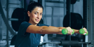 Image of woman holding dumbbells in a gym
