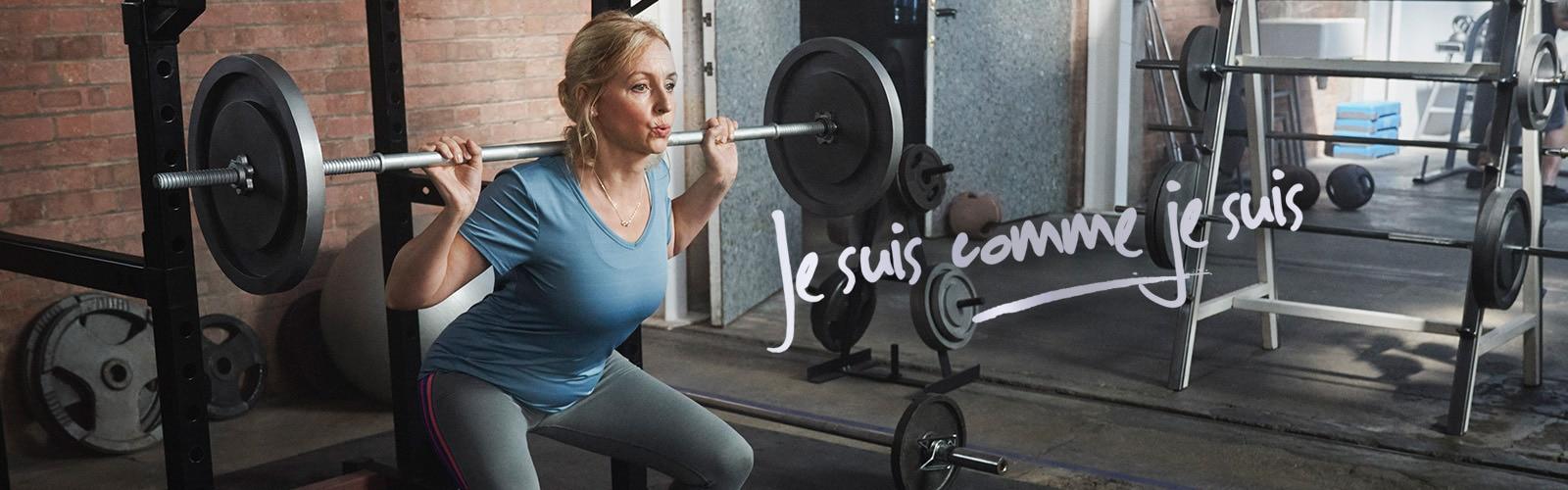 Femmesûre desoisoulevant des poids à la salle de sport