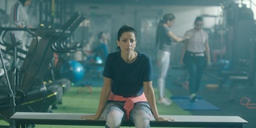 صورة لإمرأة جالسة في صالة رياضية