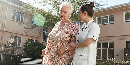 Kvinna promenerar med vårdgivare